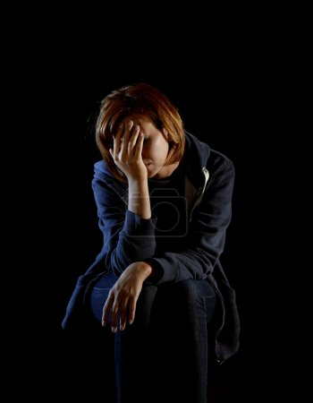 Photo for Young attractive woman suffering depression and stress sitting alone in pain and grief feeling sad and desperate isolated on black background - Royalty Free Image