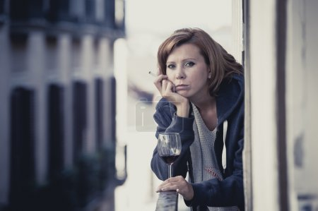 Photo for Young attractive woman suffering depression smoking and drinking wine in stress outdoors at home balcony terrace window in pain and grief feeling sad and desperate in urban background - Royalty Free Image