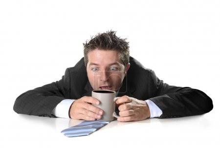 Photo for Young  addict business man in suit and tie holding cup of coffee anxious and crazy in caffeine addiction and need to keep awaken isolated on white background - Royalty Free Image
