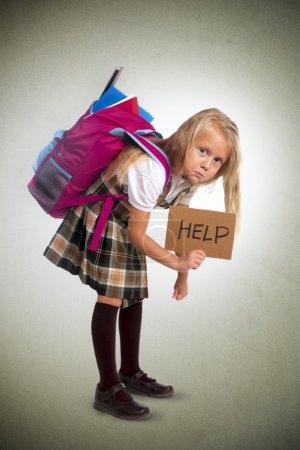 Photo pour Jeune écolière blonde tenant signe d'aide portant sac à dos lourd ou sac d'école plein causant le stress et la douleur sur le dos en raison de l'embonpoint isolé sur fond de grunge - image libre de droit