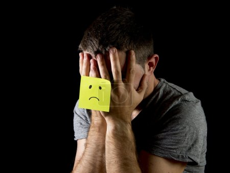 Photo for Young man suffering depression and stress sitting alone in pain and grief feeling desperate with yellow post it note sad face stuck on his hands isolated on black background - Royalty Free Image