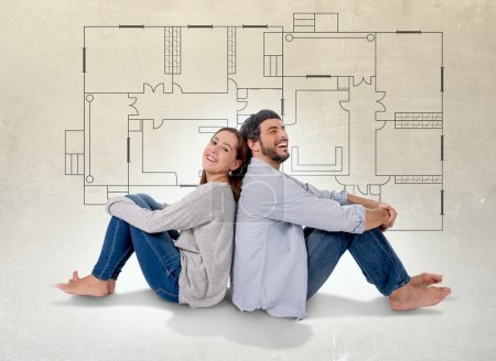 Young attractive couple in love happy together thinking and imaging blueprints , floor plan and design of new house, home, flat or apartment in real state concept