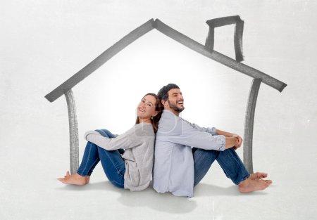 Photo pour Jeune couple attrayant et moderne amoureux souriant heureux ensemble assis sur le sol en pensant et en imaginant leur nouvelle maison, maison, appartement ou appartement dans le concept de l'état réel - image libre de droit