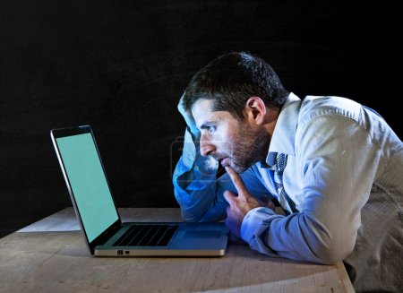 Young stressed businessman working late night on desk with computer laptop