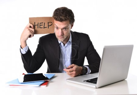 attractive businessman working in stress at computer holding help cardboard sign
