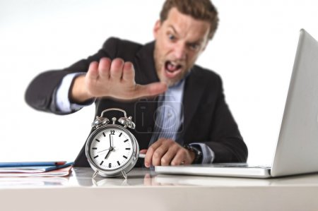 Exploited businessman at office desk stressed and frustrated with  alarm clock in out of time and deadline concept