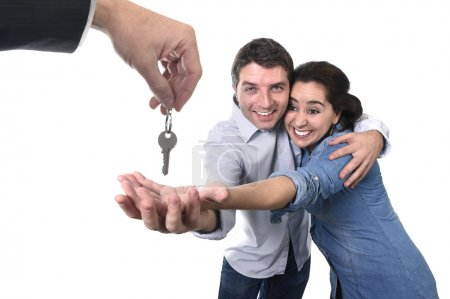 Young happy couple receiving house key new residence in real state concept