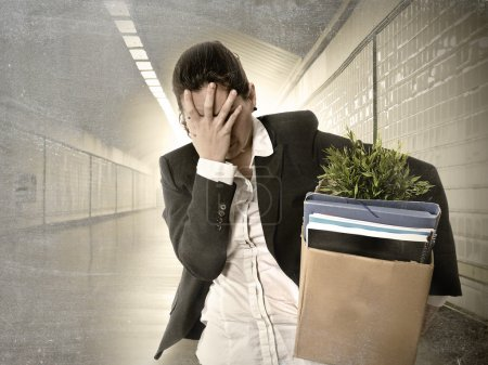 Sad depressed businesswoman carrying cardboard box fired from Job
