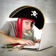 Постер, плакат: Man in pirate hat downloading music files and movies on computer laptop