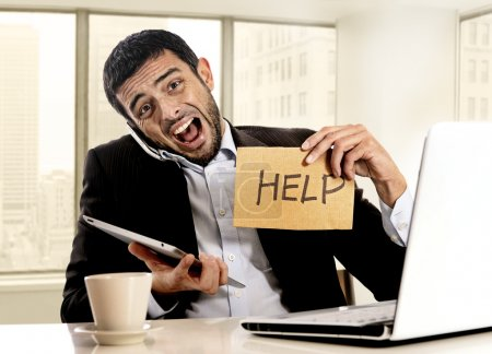 businessman in stress holding help sign multitasking overwhelmed in business district office