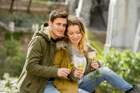 couple in love kissing tenderly on street celebrating Valentines day or anniversary cheering in Champagne