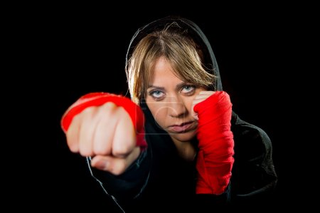 young sexy dangerous girl shadow boxing with wrapped hands and wrists training workout