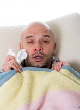 Young sick man with snotty nose having temperature infected by grippe flue influenza virus