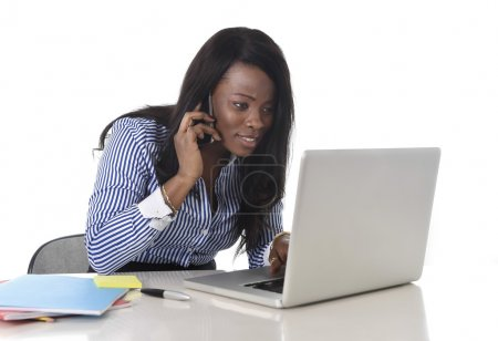 happy black ethnicity woman working at computer laptop and mobile phone relaxed