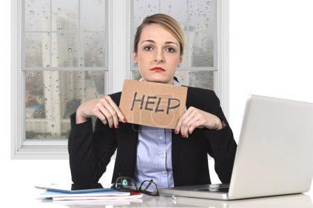 Photo pour Jeune femme d'affaires attrayante frustrée tenant un message d'aide surmenée à l'ordinateur de bureau, épuisée, désespérée sous pression et le stress avec vue triste et pluvieuse fenêtre - image libre de droit