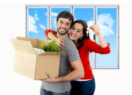 happy couple moving together in a new house unpacking cardboard