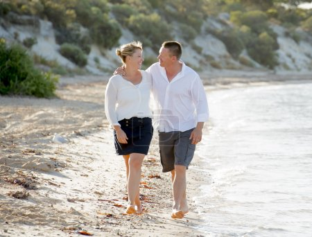 attractive beautiful  couple in love walking on the beach in romantic summer holidays