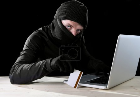 man in black holding credit card using computer laptop for criminal activity hacking password and private information