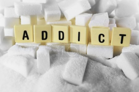 Addict block letters word on pile of sugar cubes close up in sugar addiction concept