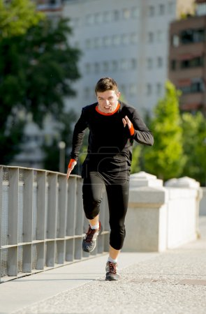 young athletic man running on urban city park in sport training session