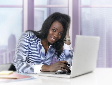 attractive black African American ethnicity woman working at computer laptop at business district office