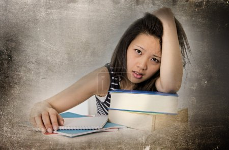 young pretty chinese asian student woman bored tired and overworked leaning on school books studying