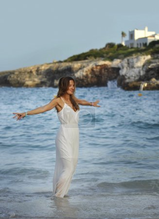 attractive and beautiful woman enjoying vacation summer holidays at Spain coast village walking on beach