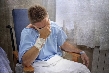 Foto de Young injured man crying in hospital room sitting alone in pain looking negative and worried for his bad health condition sitting on chair suffering depression on a grunge medical background - Imagen libre de derechos
