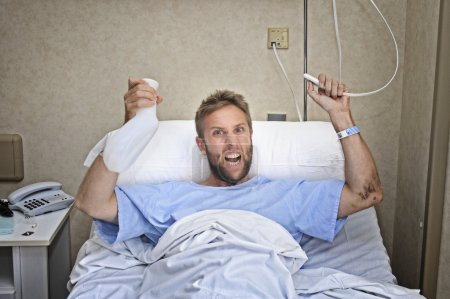 angry patient man at hospital room lying in bed pressing nurse call button holding potty