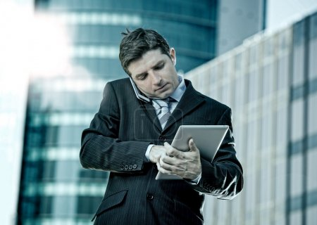 busy businessman holding digital tablet and mobile phone overworked