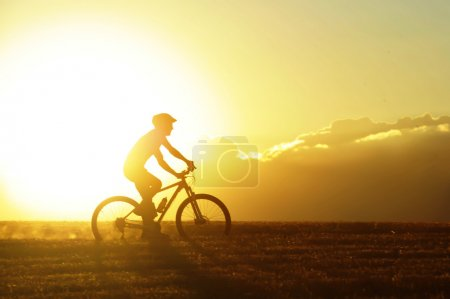 Profile silhouette of sport man cycling uphill rid...