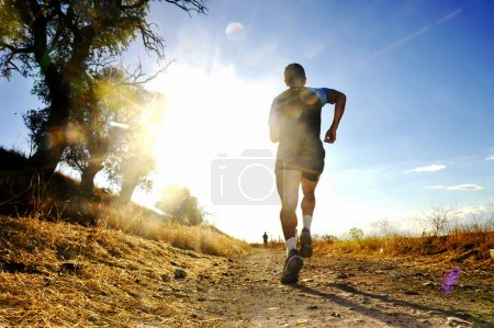 Silhouette of young sport man running off road cross country competition at summer sunset
