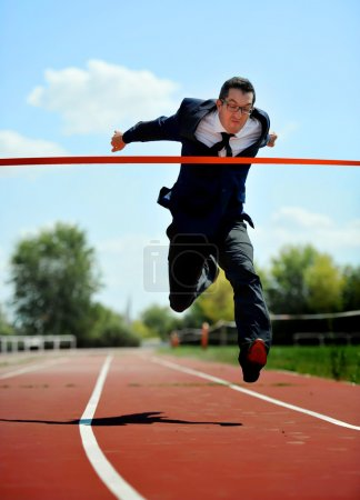 businessman running on athletic track celebrating victory in work success concept