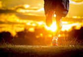 young man strong legs off trail running at amazing summer sunset in sport and healthy lifestyle