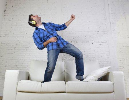 20s ou 30s homme a sauté sur l'écoute de canapé à la musique sur téléphone mobile avec un casque jouant de la guitare de l'air