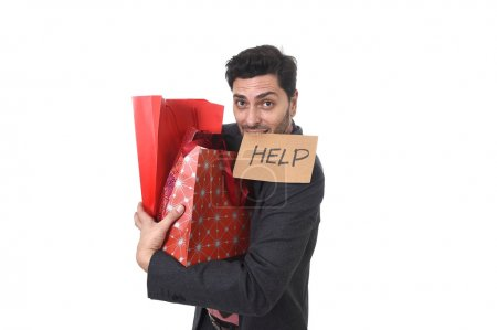 young attractive business man in stress holding lot of shopping bags and showing help sign on his mouth looking tired bored and worried