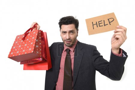 young attractive business man in stress holding lot of shopping bags and help sign looking tired bored and worried