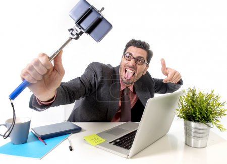 funny businessman at office desk taking selfie photo with mobile phone camera and stick
