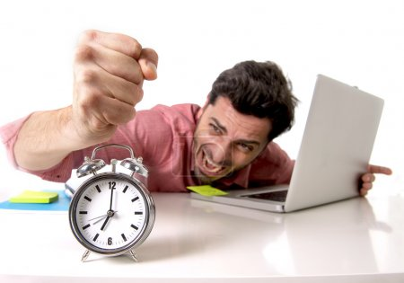 crazy businessman switching off alarm clock sitting at office desk working with computer laptop in deadline project concept