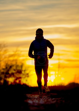 Silhouette front view of young sport man running outdoors in off road trail track with Autumn sun at orange sky sunset