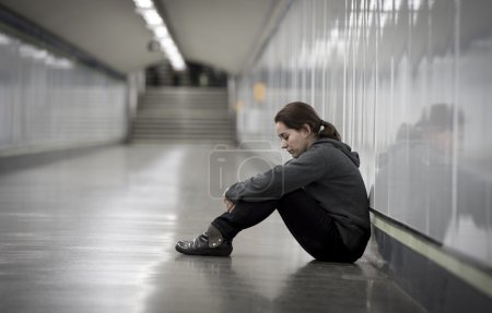 Photo for Young sad woman in pain sitting alone and depressed at urban subway tunnel ground looking worried and frustrated suffering depression in female loneliness concept - Royalty Free Image