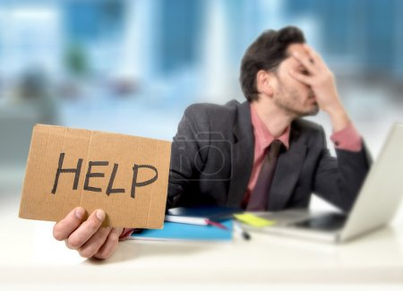 Photo for Young businessman at office desk working on computer laptop asking for help holding cardboard sign looking desperate and depressed in business stress overwhelmed and overwork concept - Royalty Free Image