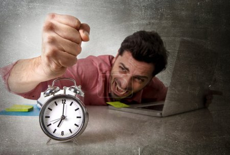 crazy businessman switching off alarm clock sitting at office working with computer deadline project concept