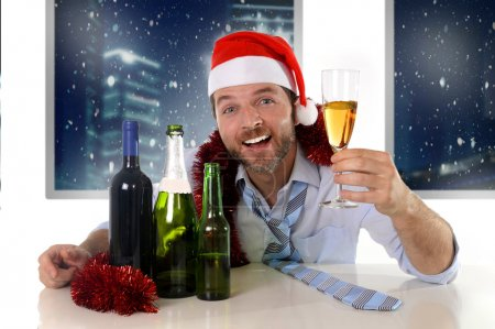 drunk happy business man in Santa hat with alcohol bottles in new year toast with champagne glass