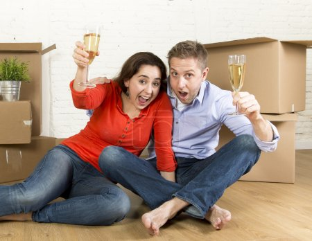 happy American couple sitting on floor unpacking together celebrating with champagne toast moving in a new house