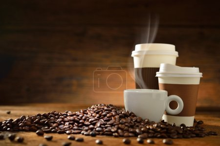 Photo for Cups of coffee with smoke and coffee beans on old wooden background - Royalty Free Image