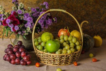 Photo pour Nature morte avec des paniers de fruits sont disposés avec un beau vase de fleurs . - image libre de droit