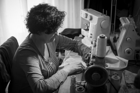 Photo for Middle aged woman sewing in black and white - Royalty Free Image