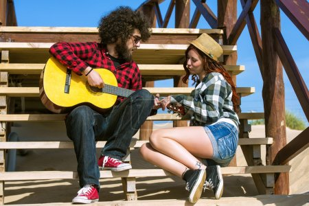 Photo for Young couple playing guitar - Royalty Free Image