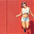 Woman jumping rope on red backgroun...